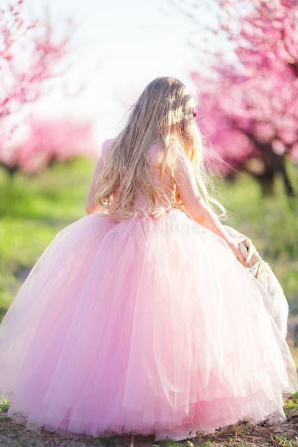 Muchacha del niño en jardín floreciente con las flores rosadas imagen de archivo