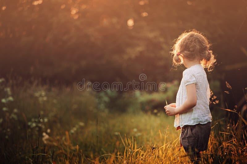 Muchacha del niño en la camisa blanca en el paseo en campo de la puesta del sol del verano imagenes de archivo