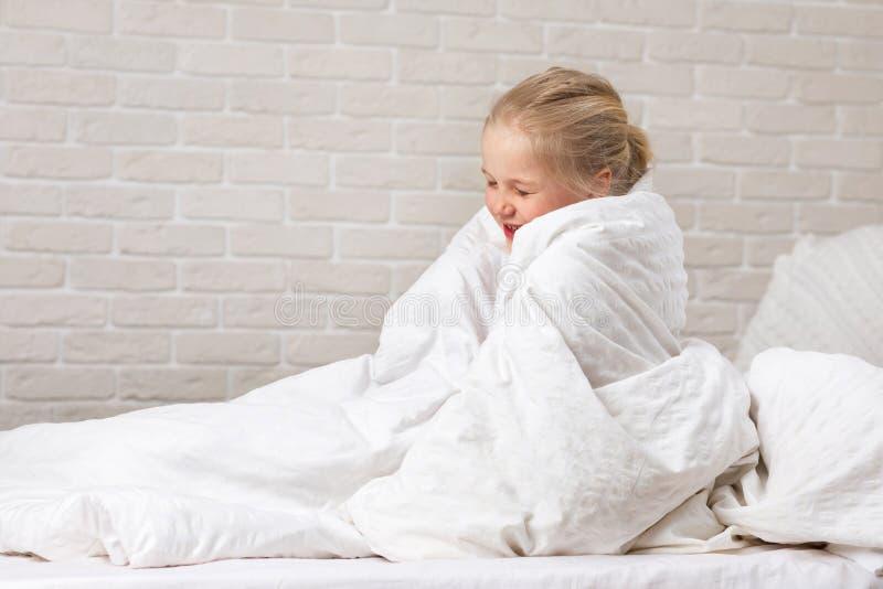 Muchacha del niño en la sentada combinada en cama imágenes de archivo libres de regalías