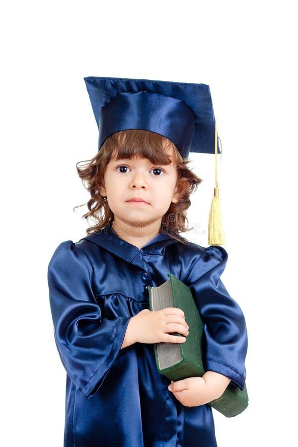 Muchacha del niño en ropa del académico con el libro imagenes de archivo