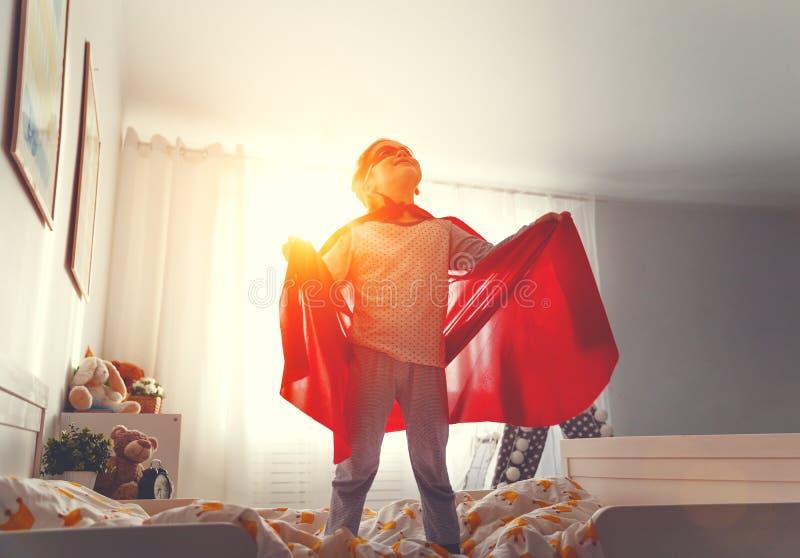 Muchacha del niño en un traje del superhéroe con la máscara y la capa roja imagen de archivo