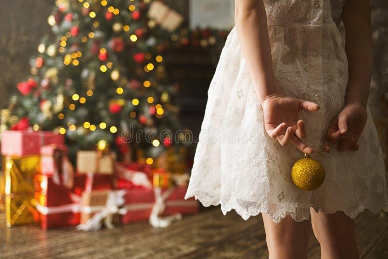 Muchacha del niño en un vestido blanco con una bola de la Navidad en sus manos que hacen frente al árbol de navidad adornado con  imagen de archivo
