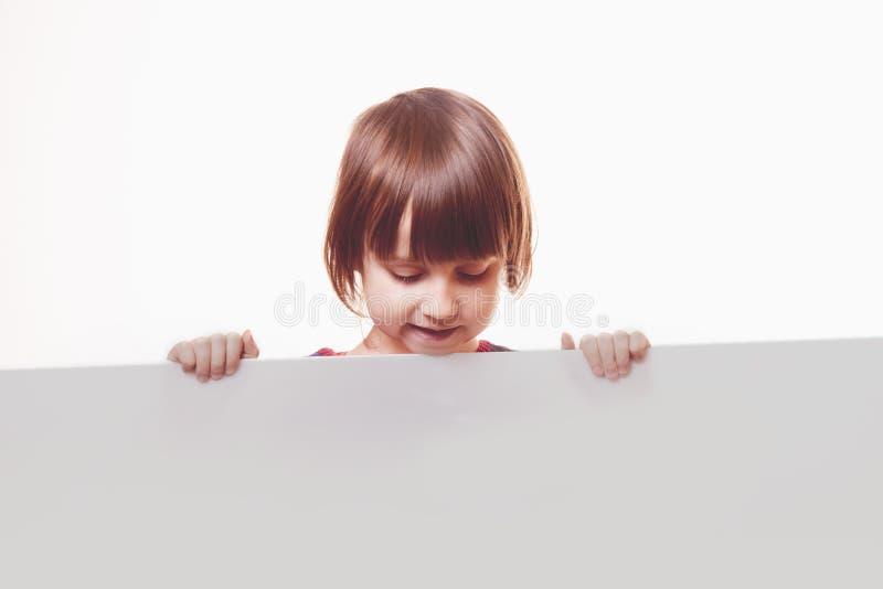 Muchacha del niño hermoso que muestra al tablero blanco en blanco para que publicidad sea insertada imagen de archivo libre de regalías
