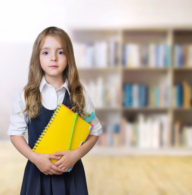 Muchacha del niño joven en fondo de la biblioteca foto de archivo libre de regalías