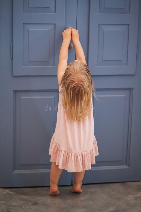 Muchacha del niño que abre la puerta imagen de archivo