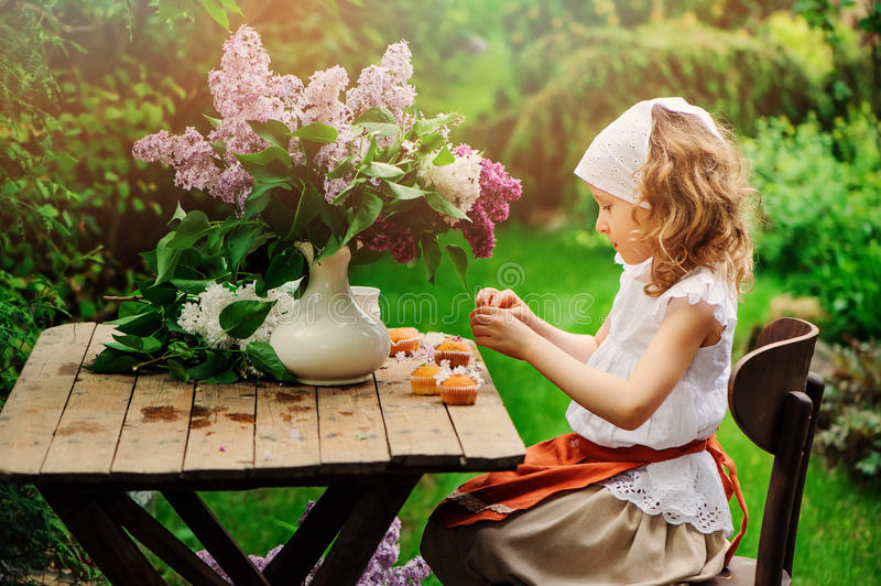 Muchacha del niño que adorna las tortas con las flores en la fiesta del té del jardín en primavera imagen de archivo libre de regalías
