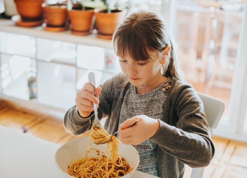 Muchacha del niño que come los espaguetis boloñés fotos de archivo libres de regalías