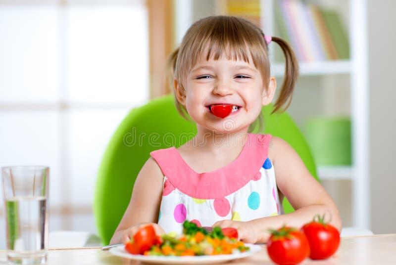 Muchacha del niño que come verduras sanas foto de archivo libre de regalías