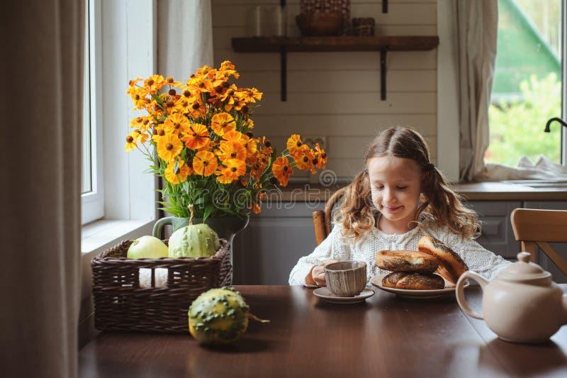 Muchacha del niño que desayuna en casa en mañana del otoño Interior moderno acogedor de la vida real en casa de campo fotos de archivo libres de regalías