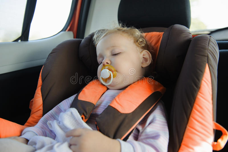 Muchacha del niño que duerme en asiento de coche de bebé fotos de archivo