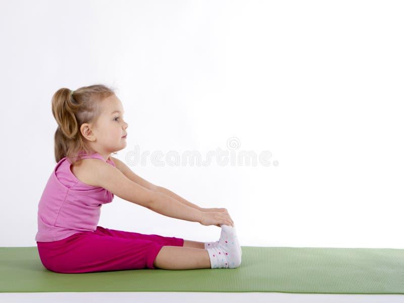 Muchacha del niño que hace ejercicios de la aptitud foto de archivo