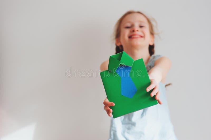 Muchacha del niño que hace la tarjeta de felicitación para el regalo para el día de padres imagenes de archivo