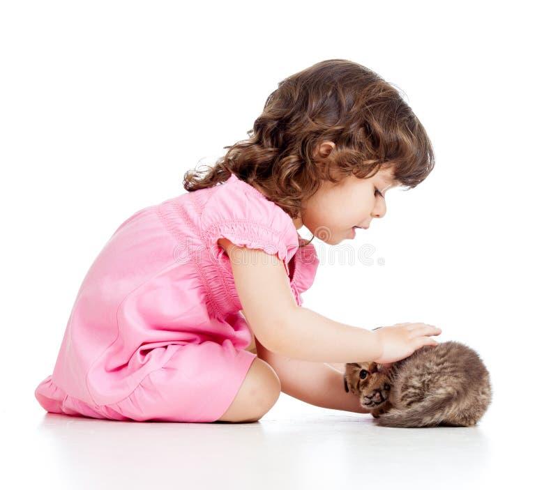Muchacha del niño que juega con el gatito del gato imágenes de archivo libres de regalías