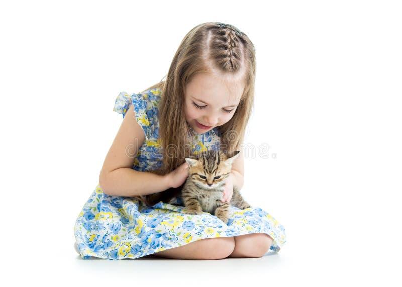 Muchacha del niño que juega con el gatito del gato fotografía de archivo