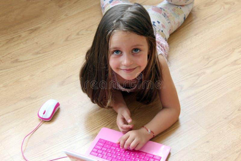 Muchacha del niño que juega con el juguete de la computadora portátil fotografía de archivo libre de regalías