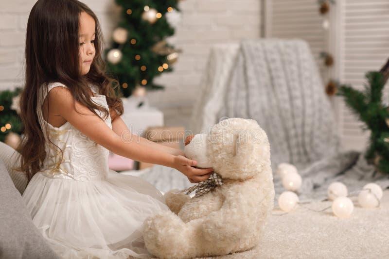 Muchacha del niño que juega con el oso de peluche cerca del árbol de navidad imagenes de archivo