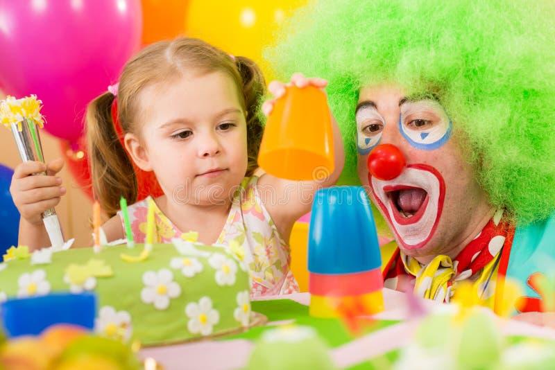 Muchacha del niño que juega con el payaso en fiesta de cumpleaños fotografía de archivo