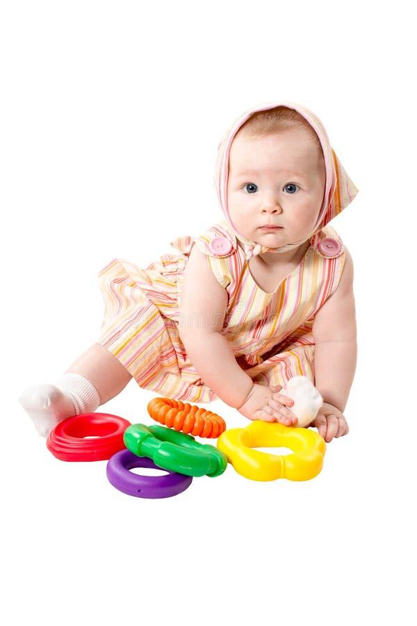 Muchacha del niño que juega con el pyramidion educativo del color del juguete aislado en el fondo blanco, juegos de Montessori imágenes de archivo libres de regalías