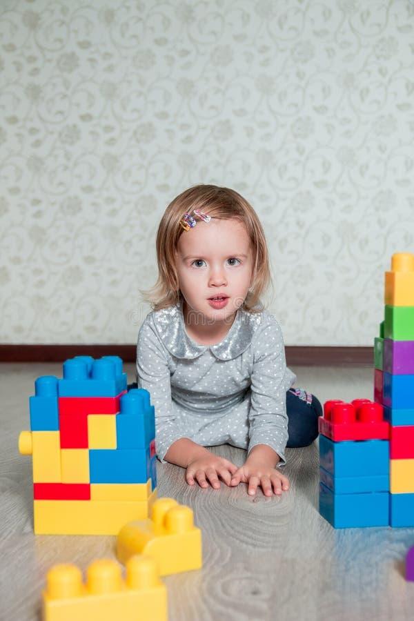 Muchacha del niño que miente cerca de bloques plásticos brillantes de la construcción Niño que juega en el piso Juguetes que se c fotografía de archivo