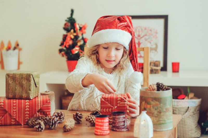 Muchacha del niño que prepara los regalos para la Navidad en casa, interior acogedor del día de fiesta fotografía de archivo libre de regalías