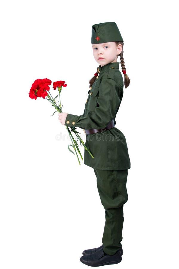 Muchacha del niño que se coloca en un uniforme con las flores rojas de lado, en un fondo blanco, y mirándole imagen de archivo
