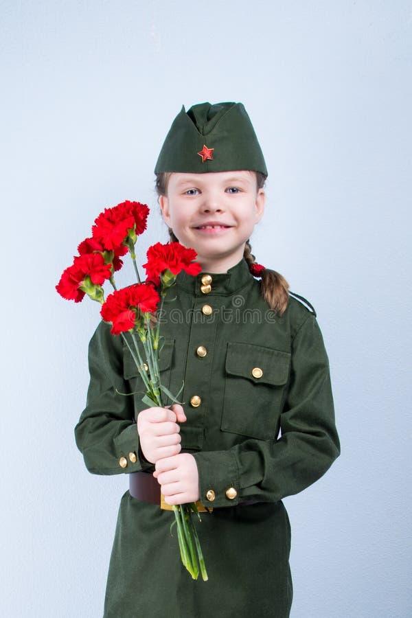 Muchacha del niño que se coloca en uniforme con las flores rojas en un fondo azul fotografía de archivo