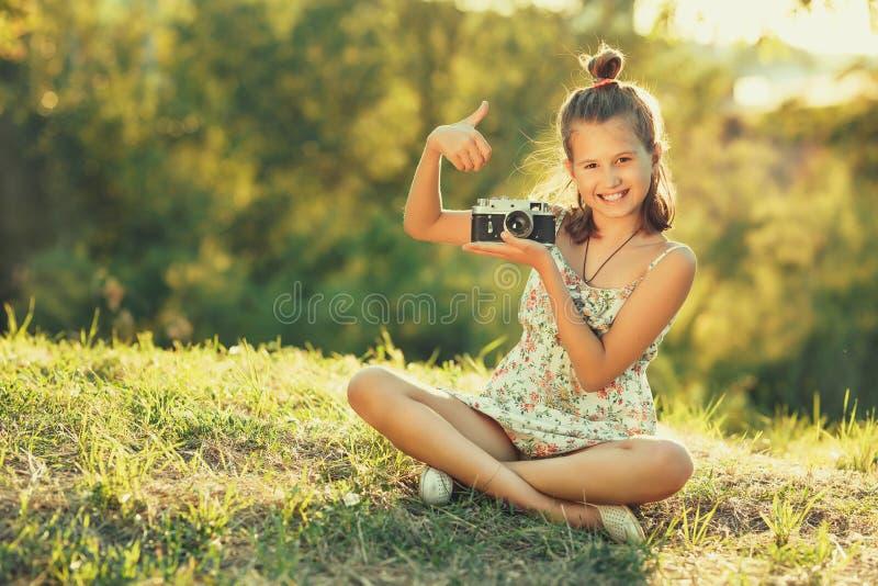 Muchacha del niño que se sienta en la hierba En sus manos ella tiene una cámara vieja de la foto y ella muestra gesto todo a la d foto de archivo libre de regalías
