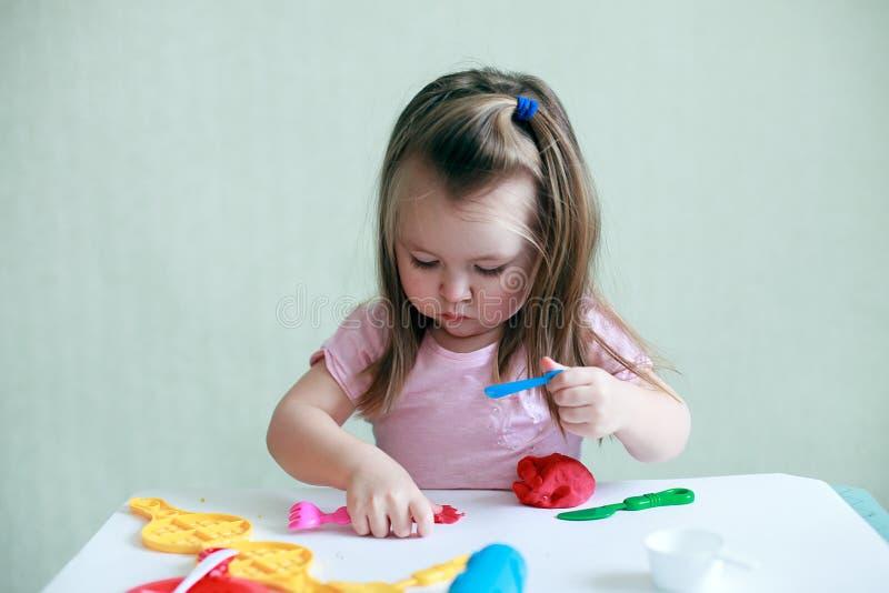 Muchacha del niño que se sienta en la tabla que juega con la arcilla colorida interior, el concepto de educación preescolar y la  imagen de archivo