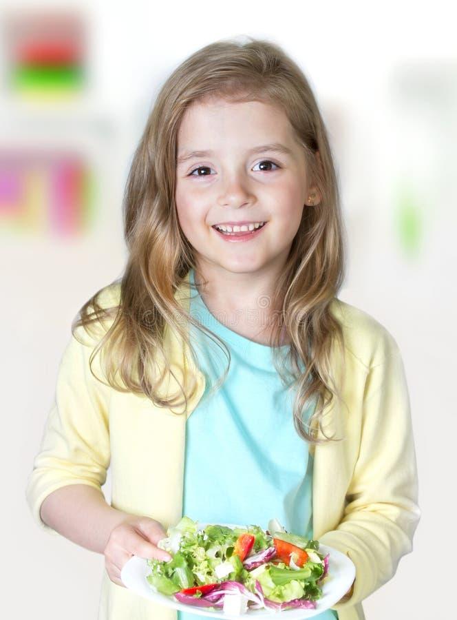 Muchacha del niño que sonríe sosteniendo la ensalada fresca Nutrición sana imagenes de archivo