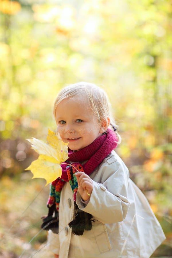 Muchacha del niño que sostiene la hoja amarilla foto de archivo libre de regalías