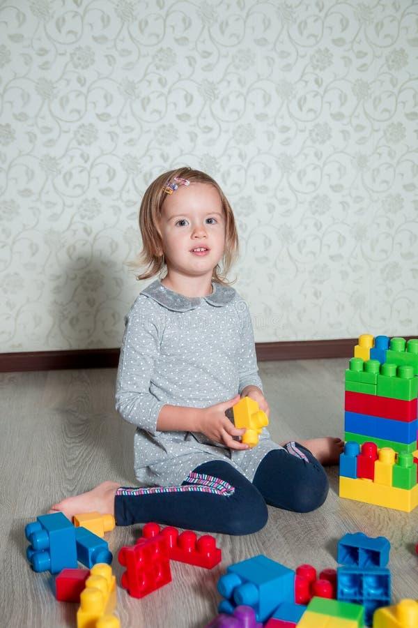 Muchacha del niño que tiene la diversión y estructura de los bloques plásticos brillantes de la construcción fotografía de archivo libre de regalías