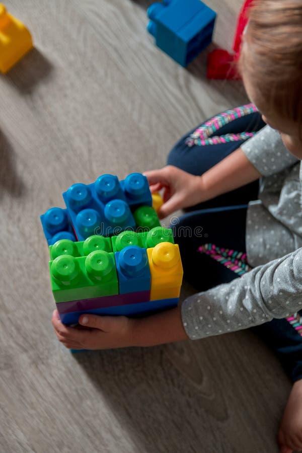 Muchacha del niño que tiene la diversión y estructura de los bloques plásticos brillantes de la construcción foto de archivo libre de regalías