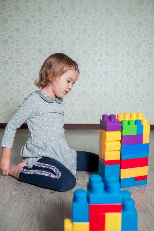 Muchacha del niño que tiene la diversión y estructura de los bloques plásticos brillantes de la construcción imágenes de archivo libres de regalías