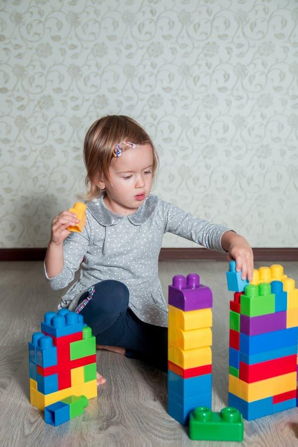 Muchacha del niño que tiene la diversión y estructura de los bloques plásticos brillantes de la construcción fotos de archivo libres de regalías