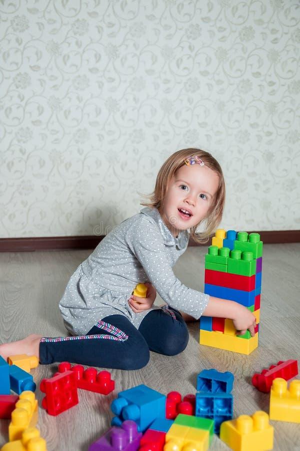 Muchacha del niño que tiene la diversión y estructura de los bloques plásticos brillantes de la construcción Niño que juega en el imagen de archivo libre de regalías