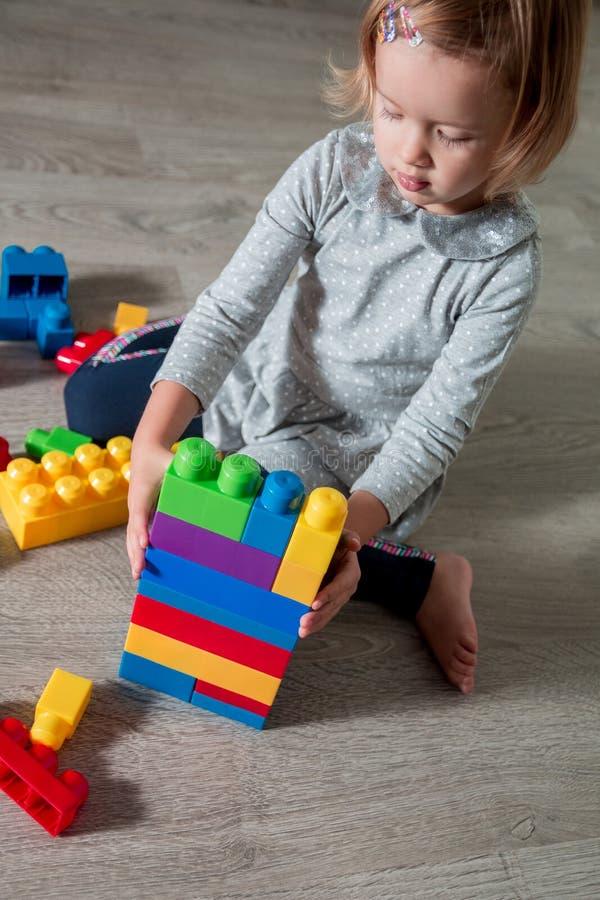 Muchacha del niño que tiene la diversión y estructura de los bloques plásticos brillantes de la construcción Niño que juega en el imagen de archivo