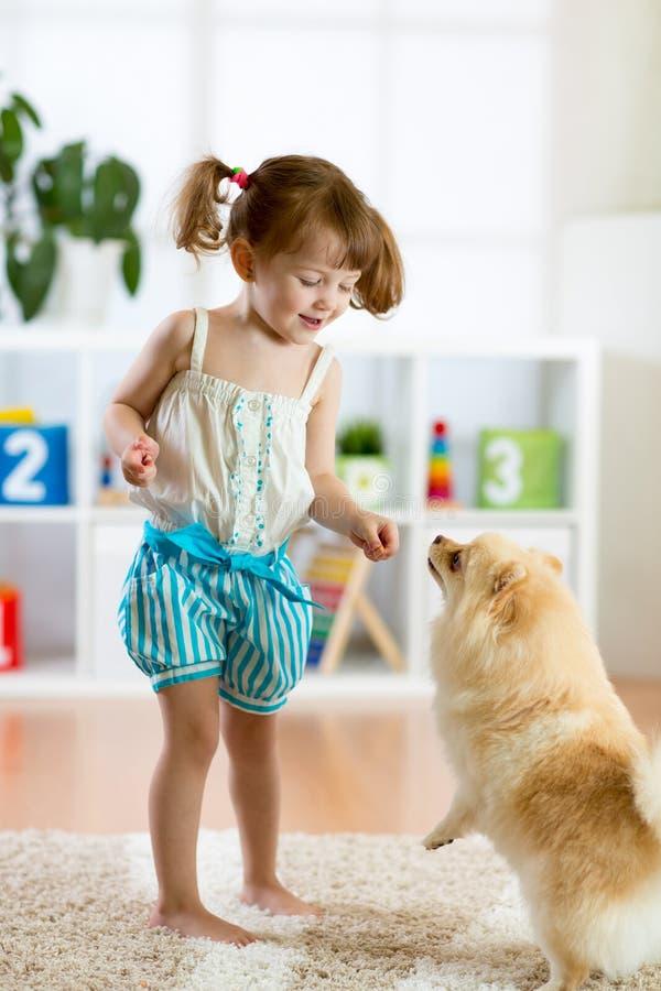 Muchacha del niño y perro lindo en casa fotografía de archivo libre de regalías