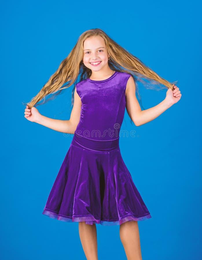 Muchacha del ni?o con el vestido largo del desgaste del pelo en fondo azul Peinado para el bailar?n C?mo hacer el peinado ordenad fotografía de archivo