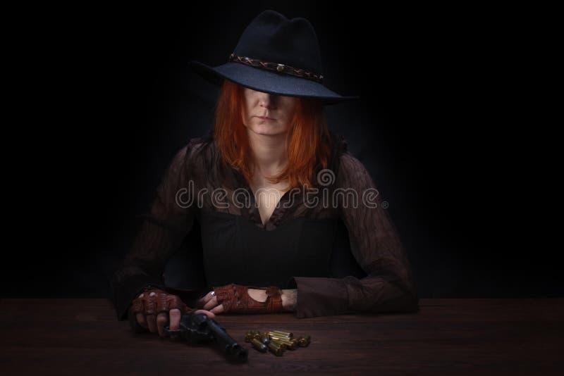 muchacha del oeste salvaje con el arma del revólver que se sienta en la tabla con la munición y monedas de plata imágenes de archivo libres de regalías