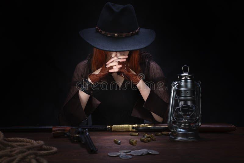 muchacha del oeste salvaje con el arma del rev?lver que se sienta en la tabla con la munici?n y monedas de plata foto de archivo libre de regalías