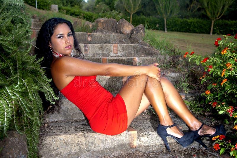Muchacha del origen del este con el vestido rojo en actitud atractiva foto de archivo