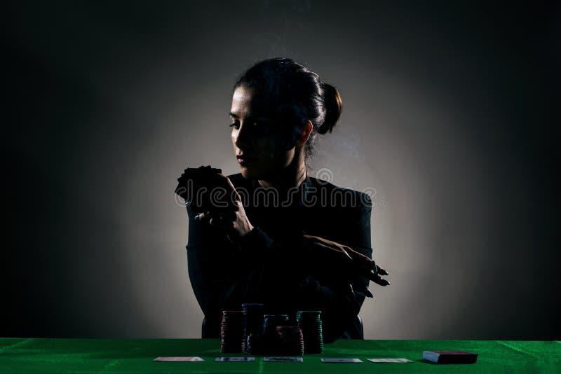 muchacha del póker de la silueta con un cigarro imagenes de archivo