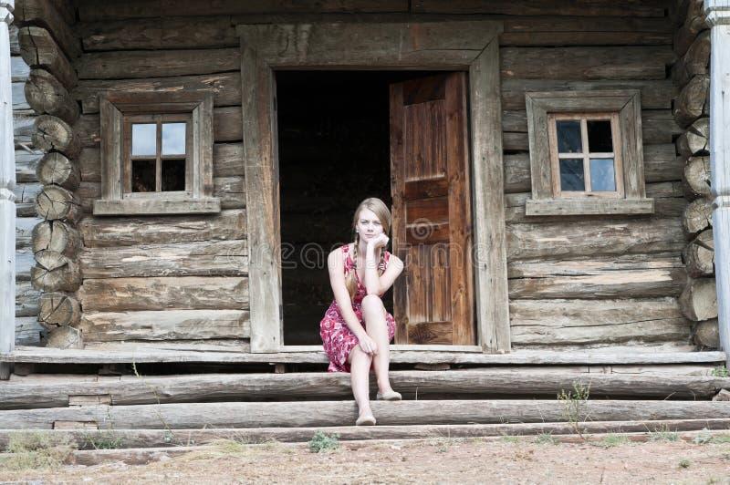 Muchacha del país que se sienta en el pórtico de una casa de madera vieja fotos de archivo libres de regalías