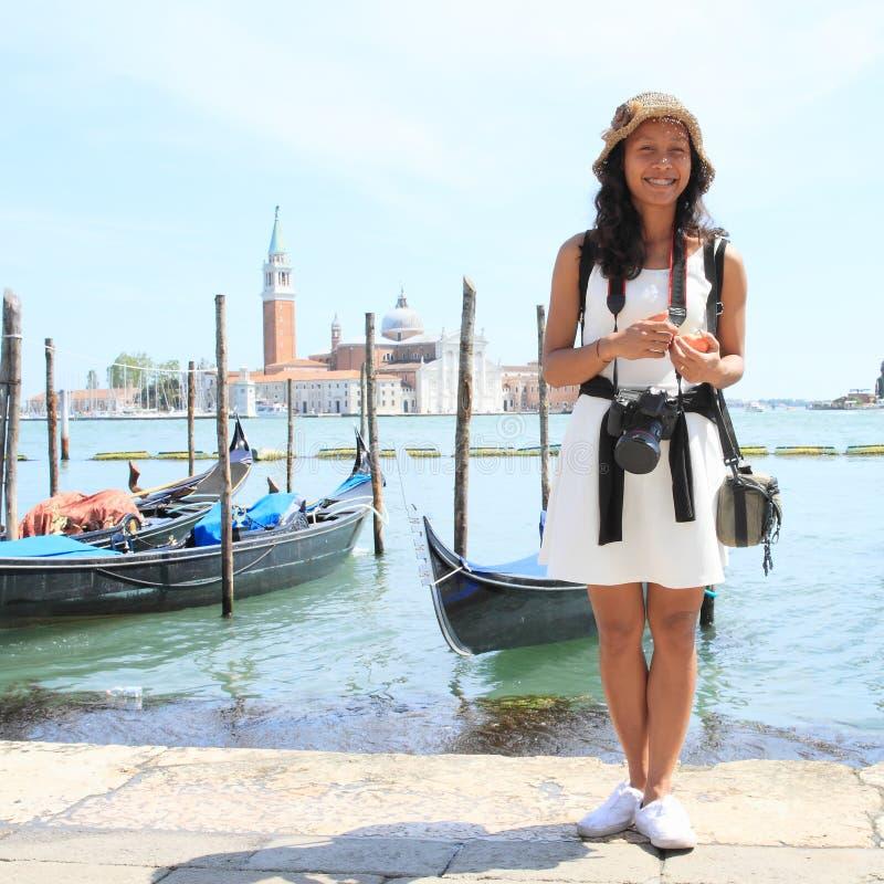 Muchacha del Papuan delante de las góndolas en puerto en Venecia imagen de archivo