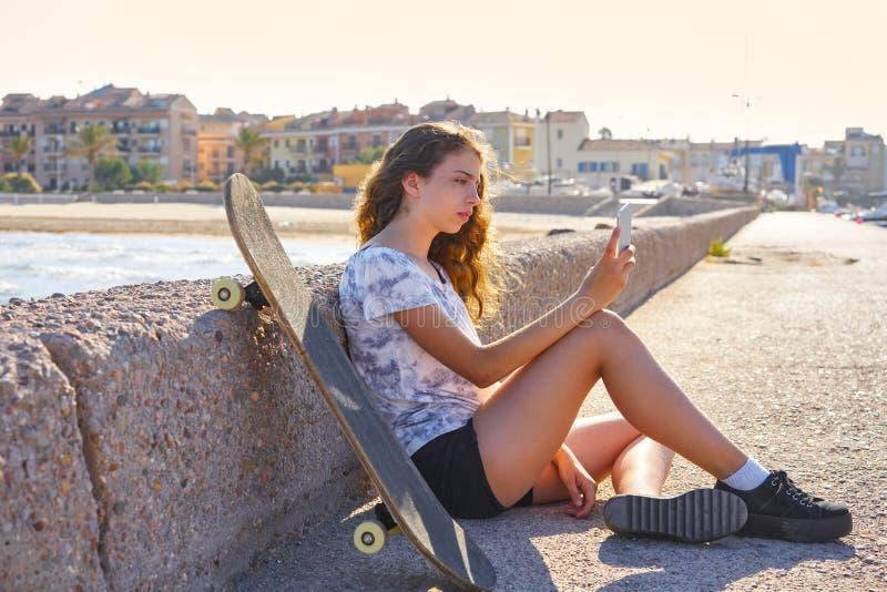 Muchacha del patín de ruedas con la sentada del smartphone imagen de archivo