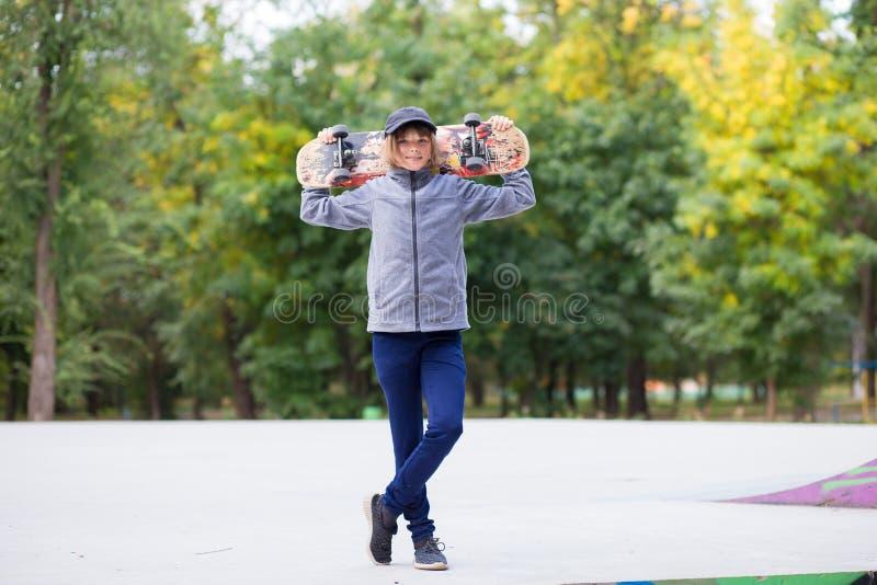Muchacha del patinador en el skatepark que mueve encendido el monopatín al aire libre foto de archivo