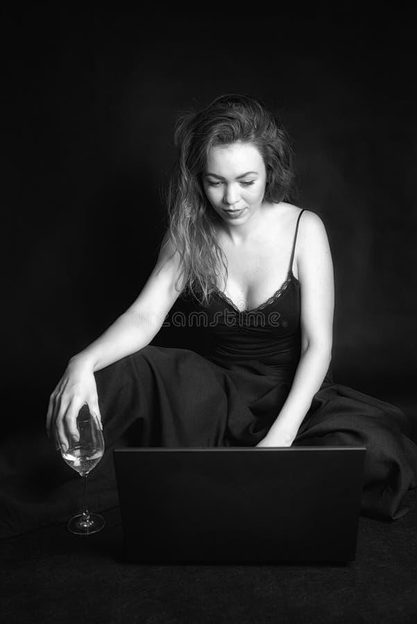 Muchacha del pelirrojo con el ordenador portátil y el vidrio de vino imagenes de archivo
