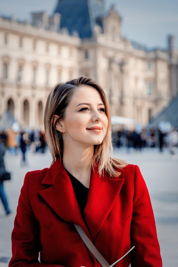 Muchacha del pelirrojo en capa roja y bolso en la calle parisiense imagenes de archivo