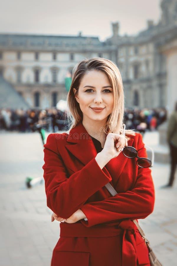 Muchacha del pelirrojo en capa roja y bolso en la calle parisiense imagen de archivo libre de regalías