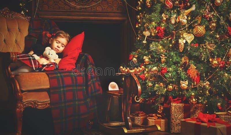 Muchacha del pequeño niño que duerme cerca de un árbol de navidad fotografía de archivo
